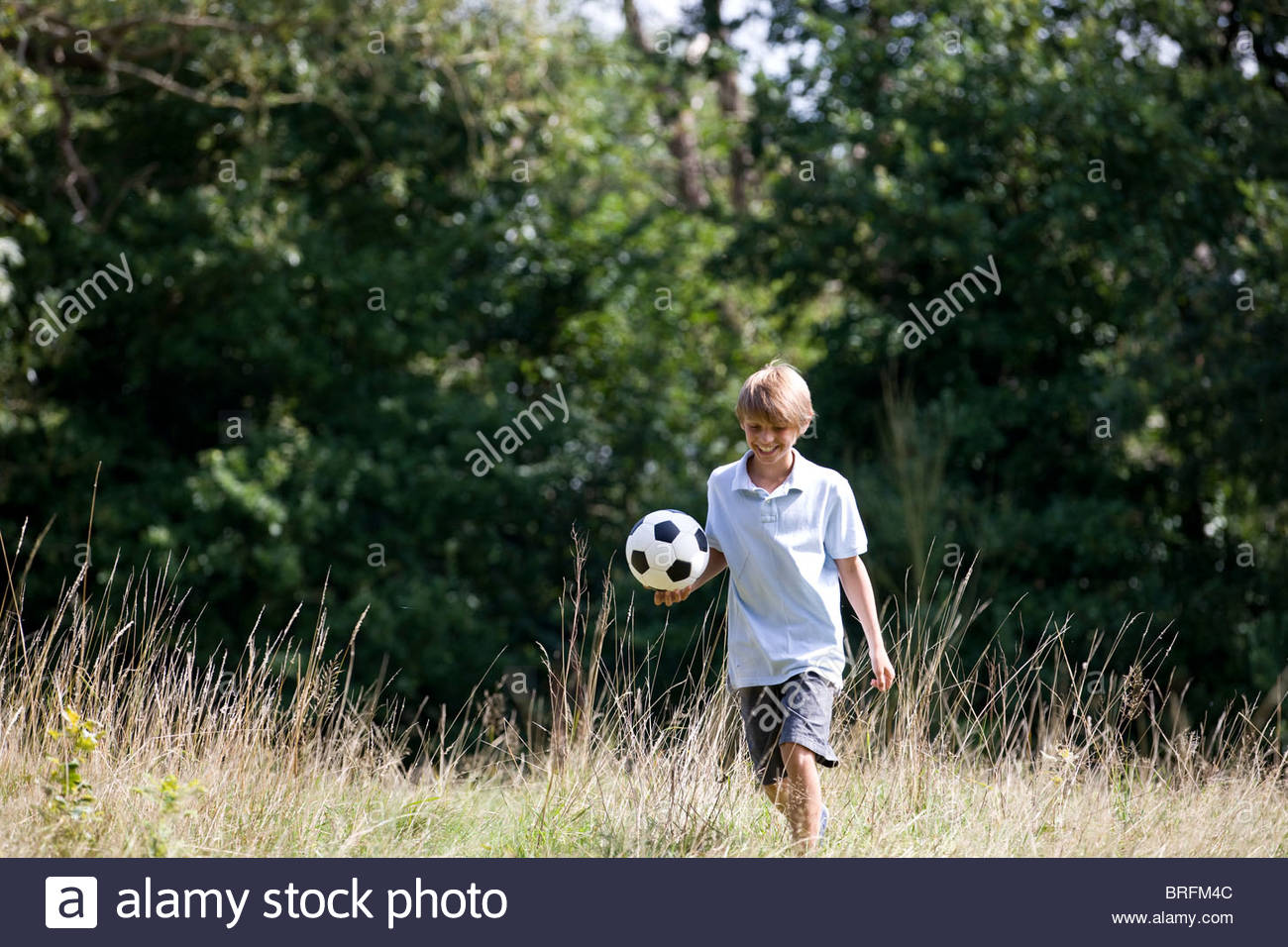 A young boy playing football in a field - Stock Image