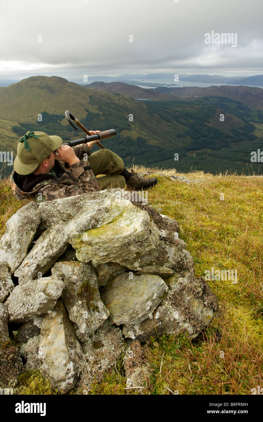 Scottish deer stalker on top of a mountain spying for deer using a three draw telescope - Stock Image