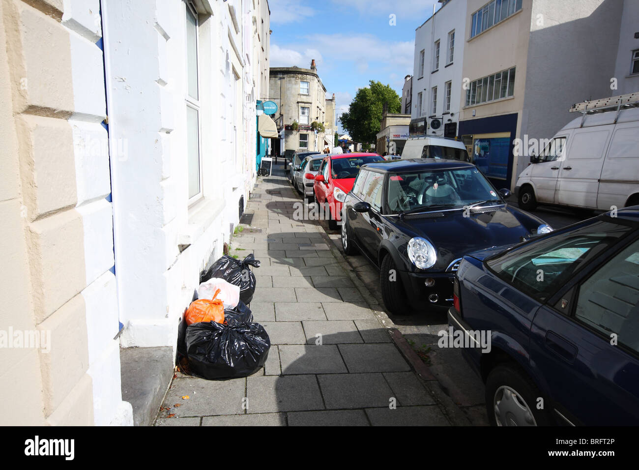 Rubbish bags on pavement outside house in Bristol street - Stock Image