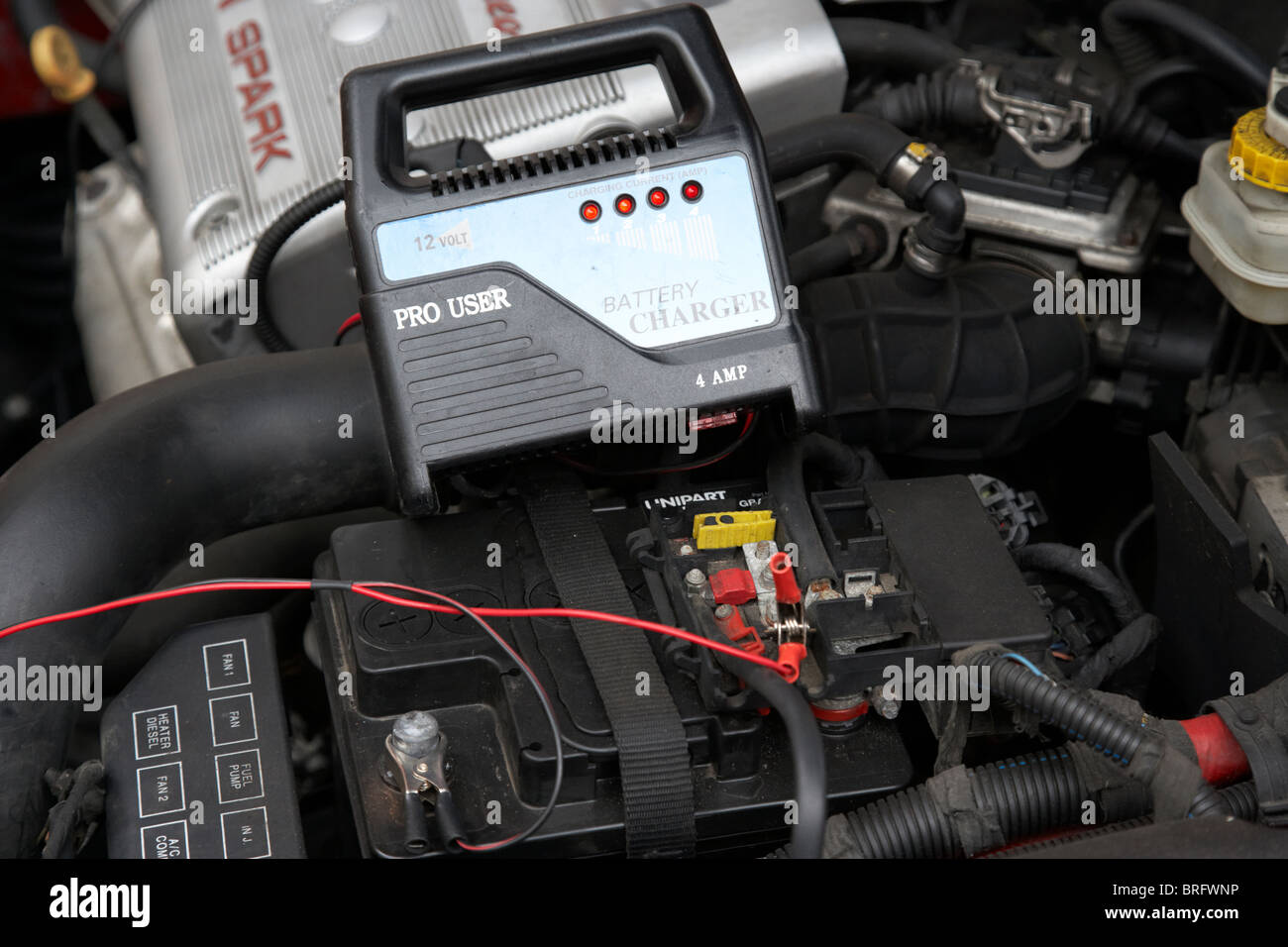 mains car battery charger charging flat car battery in cold weather - Stock Image