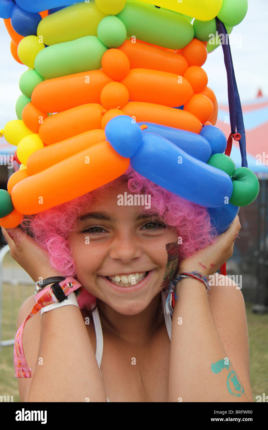 A  girl at Camp Bestival, the family friendly festival in Dorset, wearing a balloon hat. - Stock Image