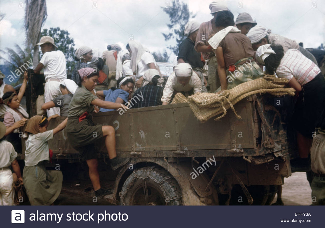 Japanese civilians board a truck to go work in their gardens. - Stock Image