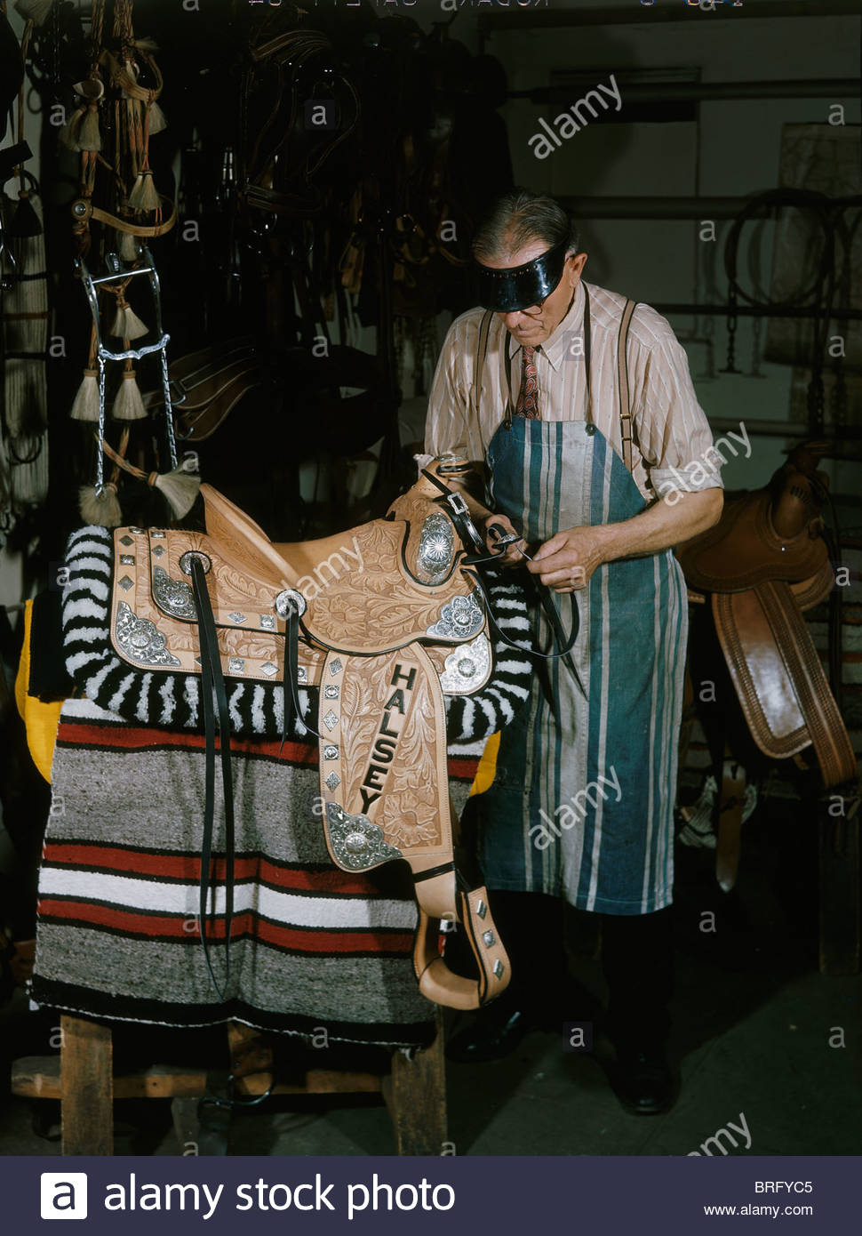 A craftsman makes tooled leather saddle with silver ornamentation. - Stock Image