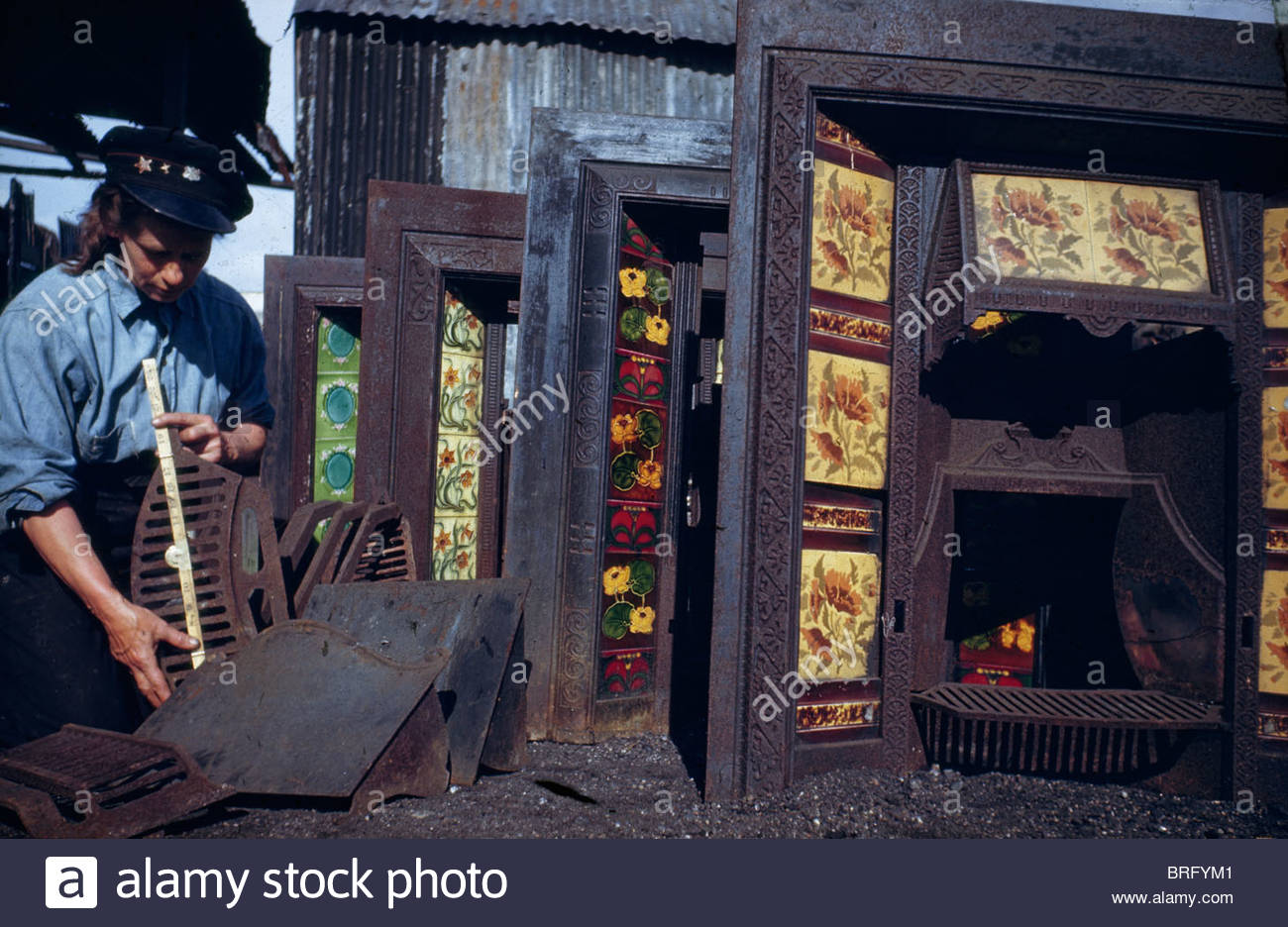 A woman salvages fireplace grates after bombing during World War II. - Stock Image