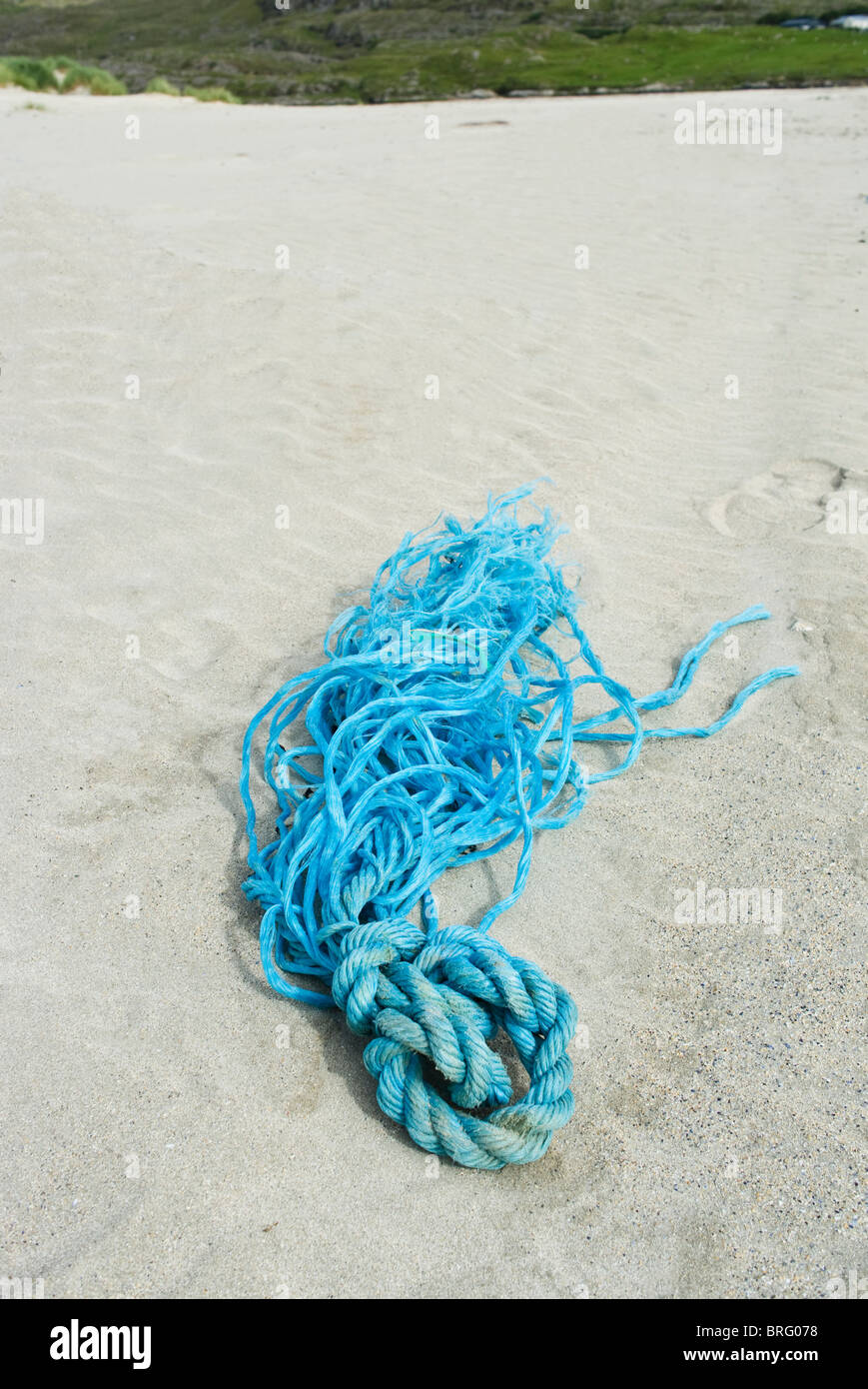 A discarded skein of blue rope on a sandy beach - Stock Image