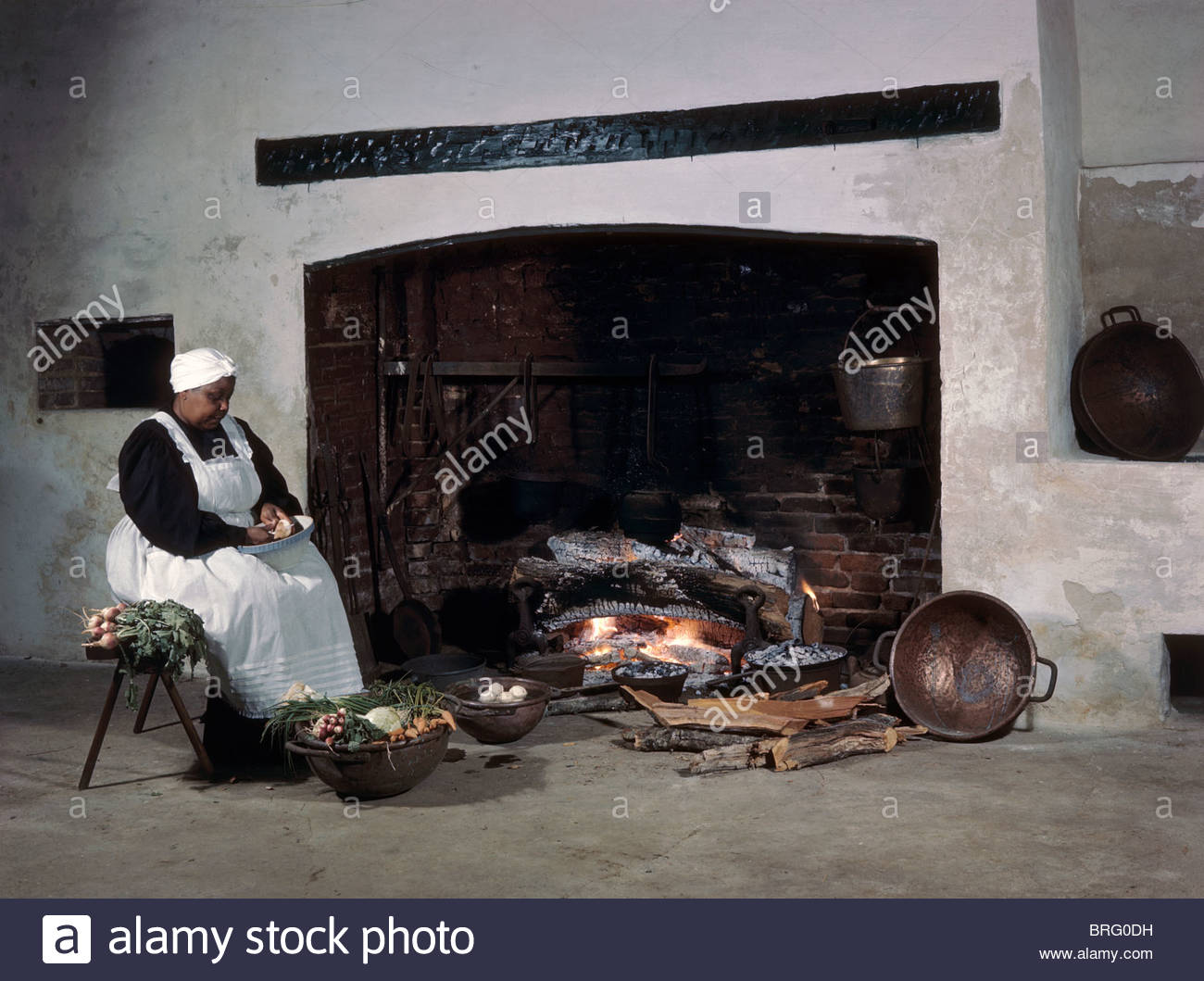 Woman in period costume works in front of large kitchen fireplace. - Stock Image