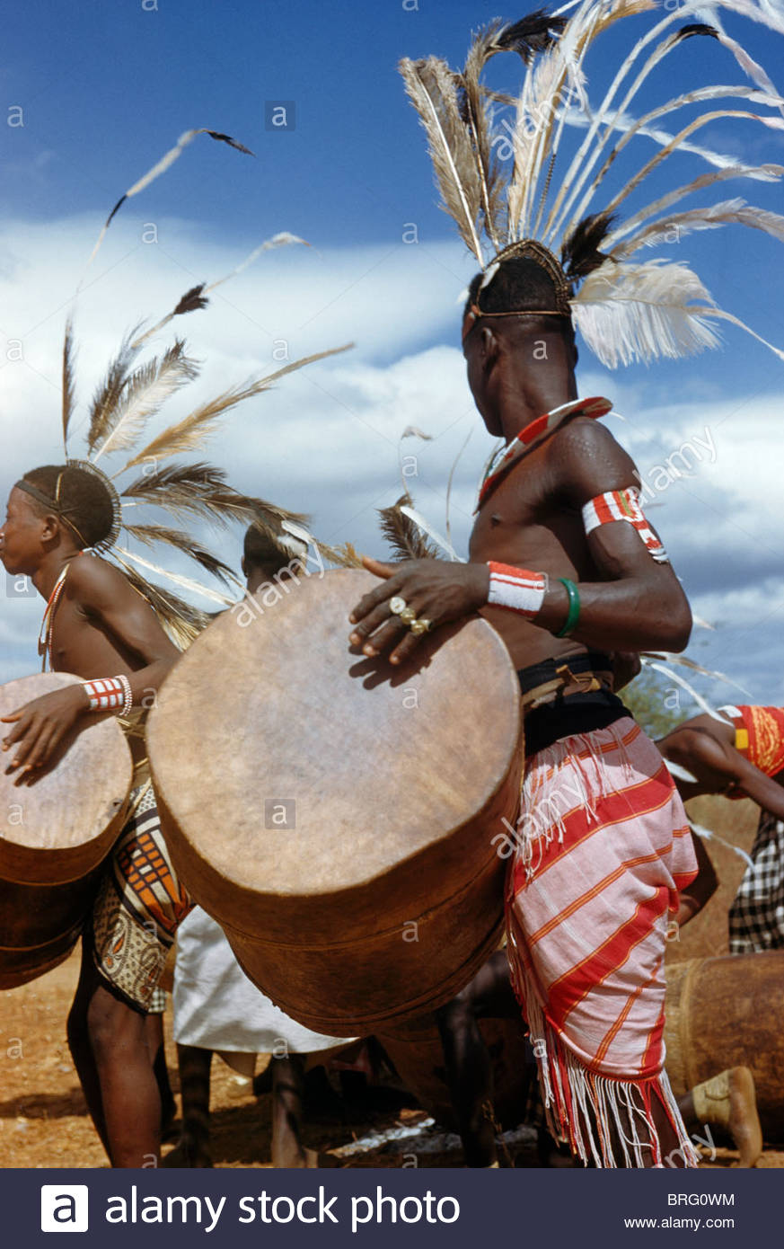 A Wakamba man beats a drum with his hands for a dance. - Stock Image