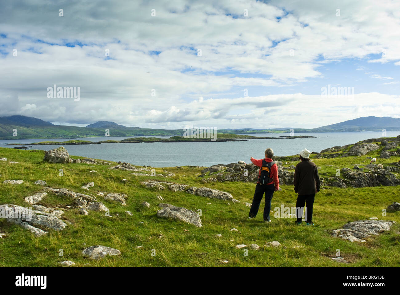 Two walkers viewing the landscape at Thallabawn strand, County Mayo, Ireland - Stock Image
