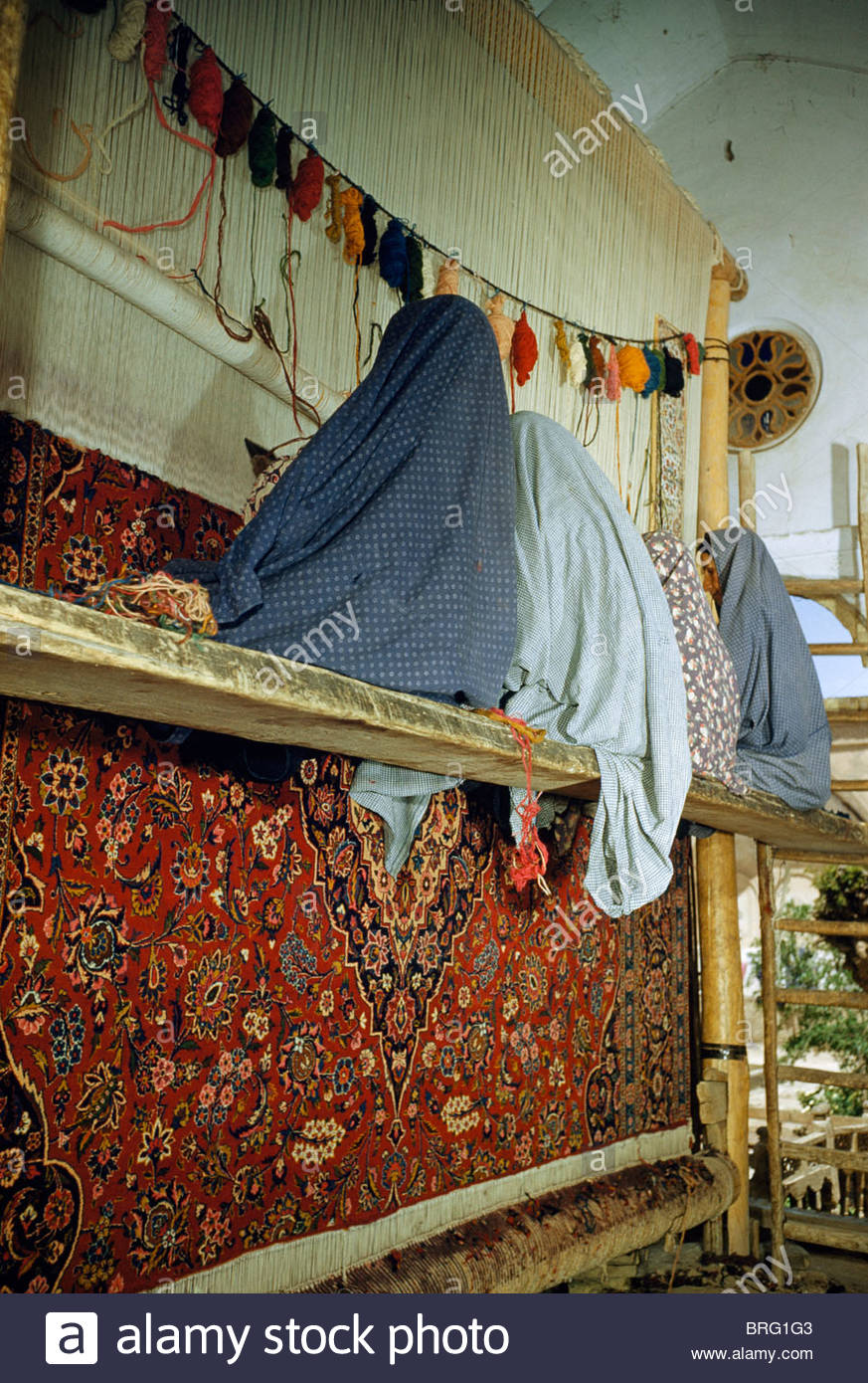 Cloaked women sit on a scaffold to make a rug in a home workshop. - Stock Image