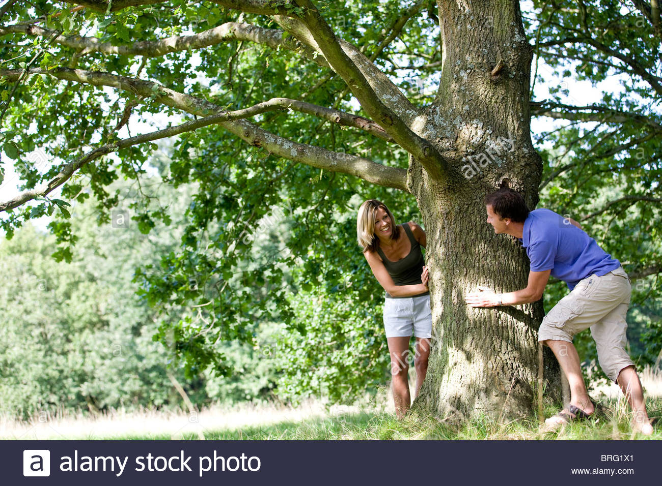 A middle aged couple playing hide and seek - Stock Image
