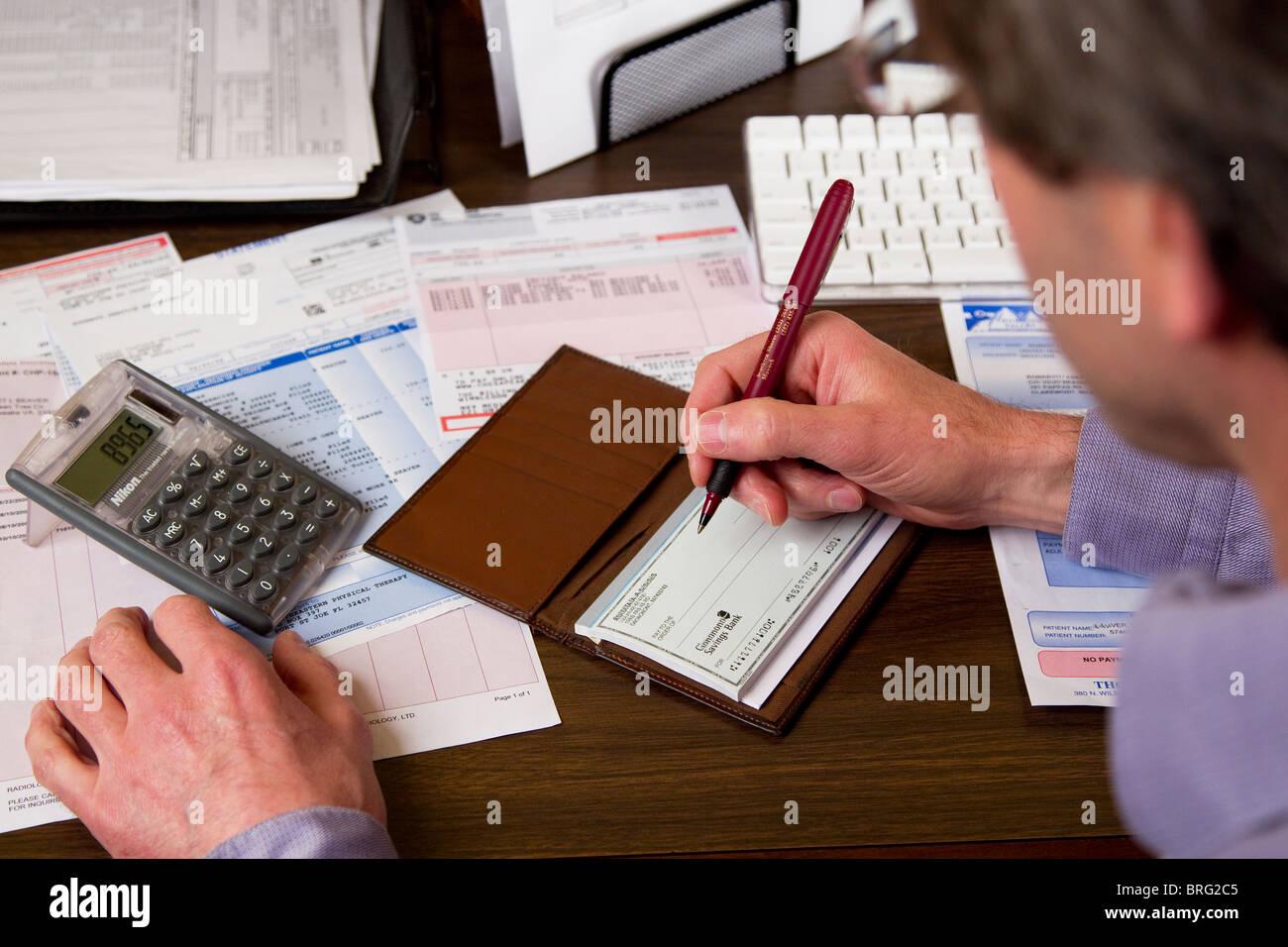 Man paying bills doing paperwork finances - Stock Image