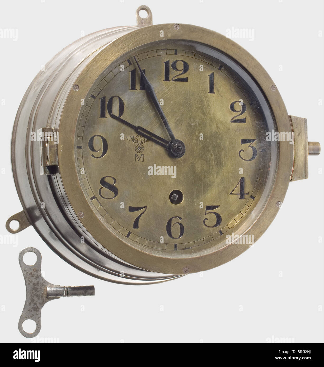 A ship's bulkhead clock., Brass case (small dents, blackening removed) with three loops for hanging, stamped - Stock Image