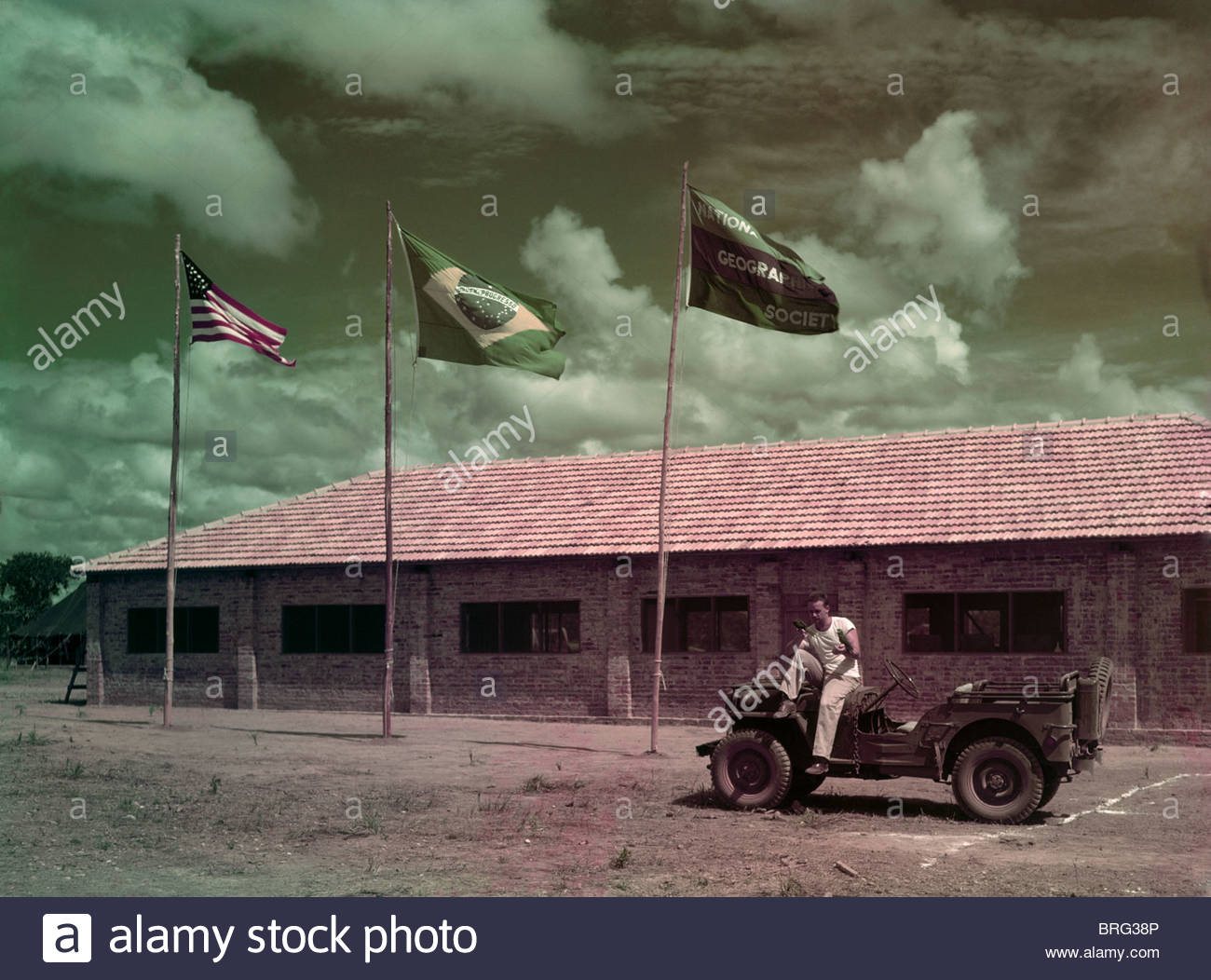 Man sets on jeep in front of a scientific expedition's mess hall. - Stock Image