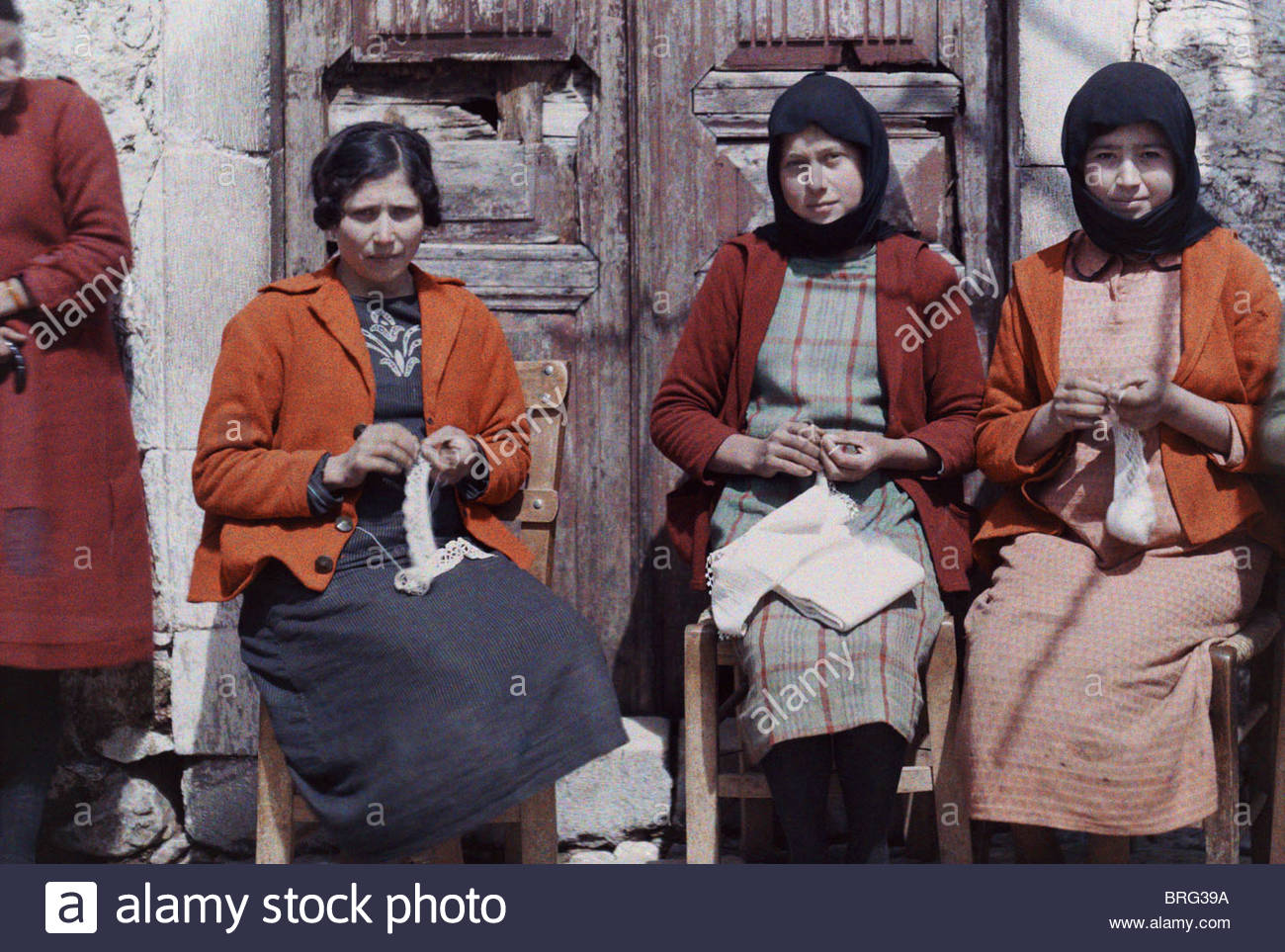 Three women sit and do needlework. - Stock Image