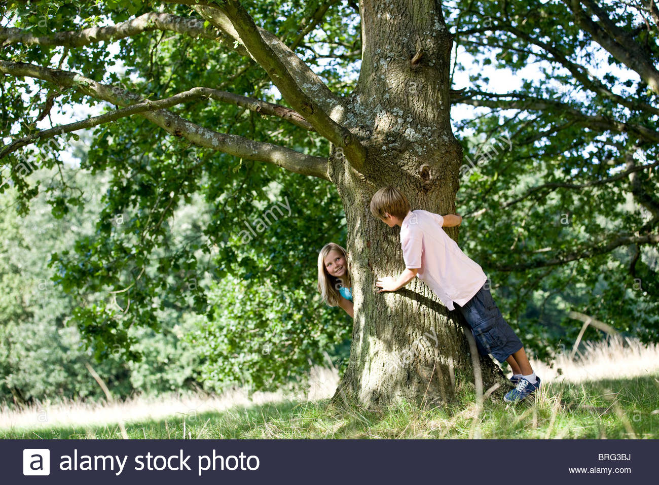 A young boy and girl playing hide and seek - Stock Image