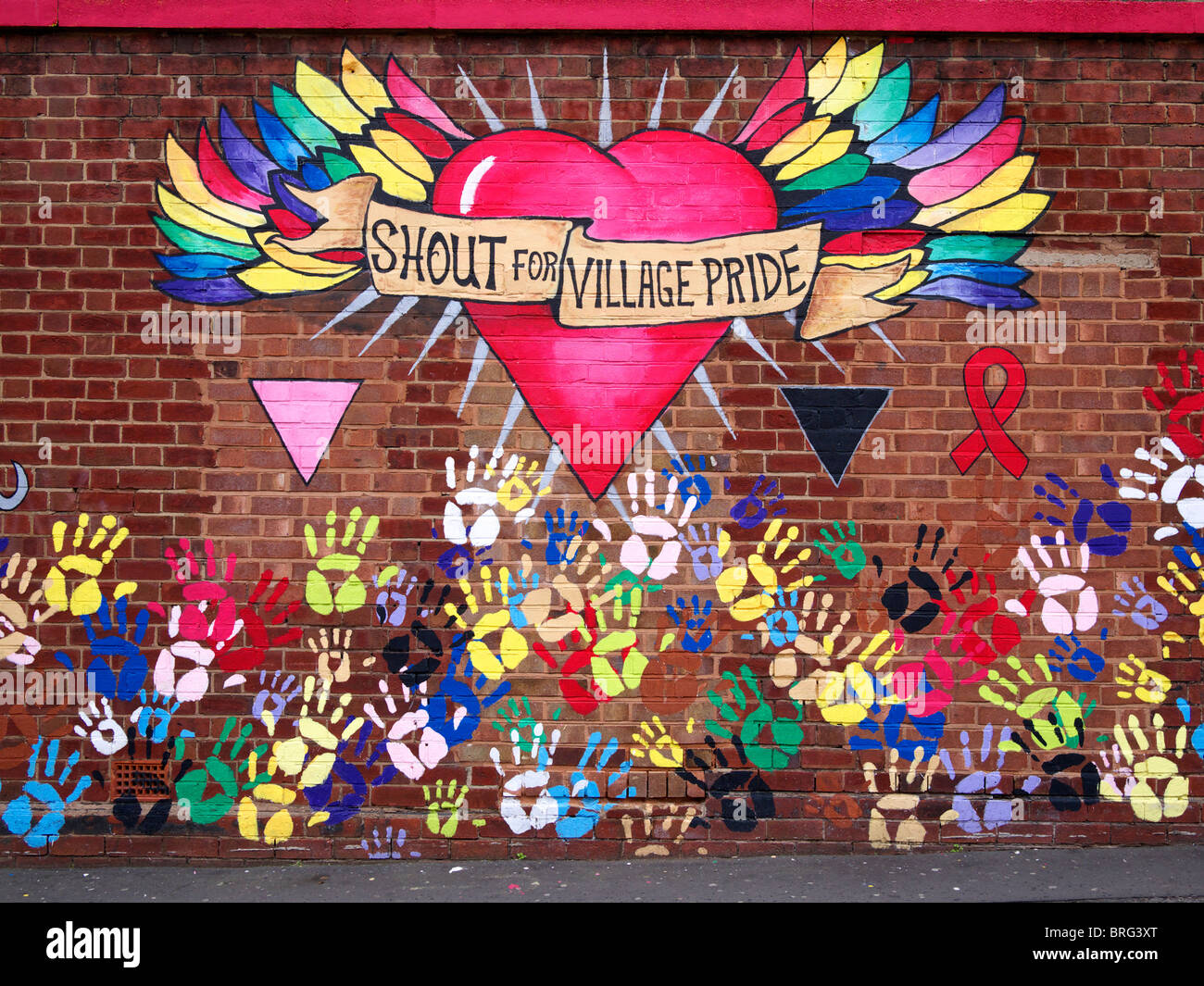 Gay village sign painted on a brick wall near Hurst Street part of the city's gay area Birmingham UK - Stock Image