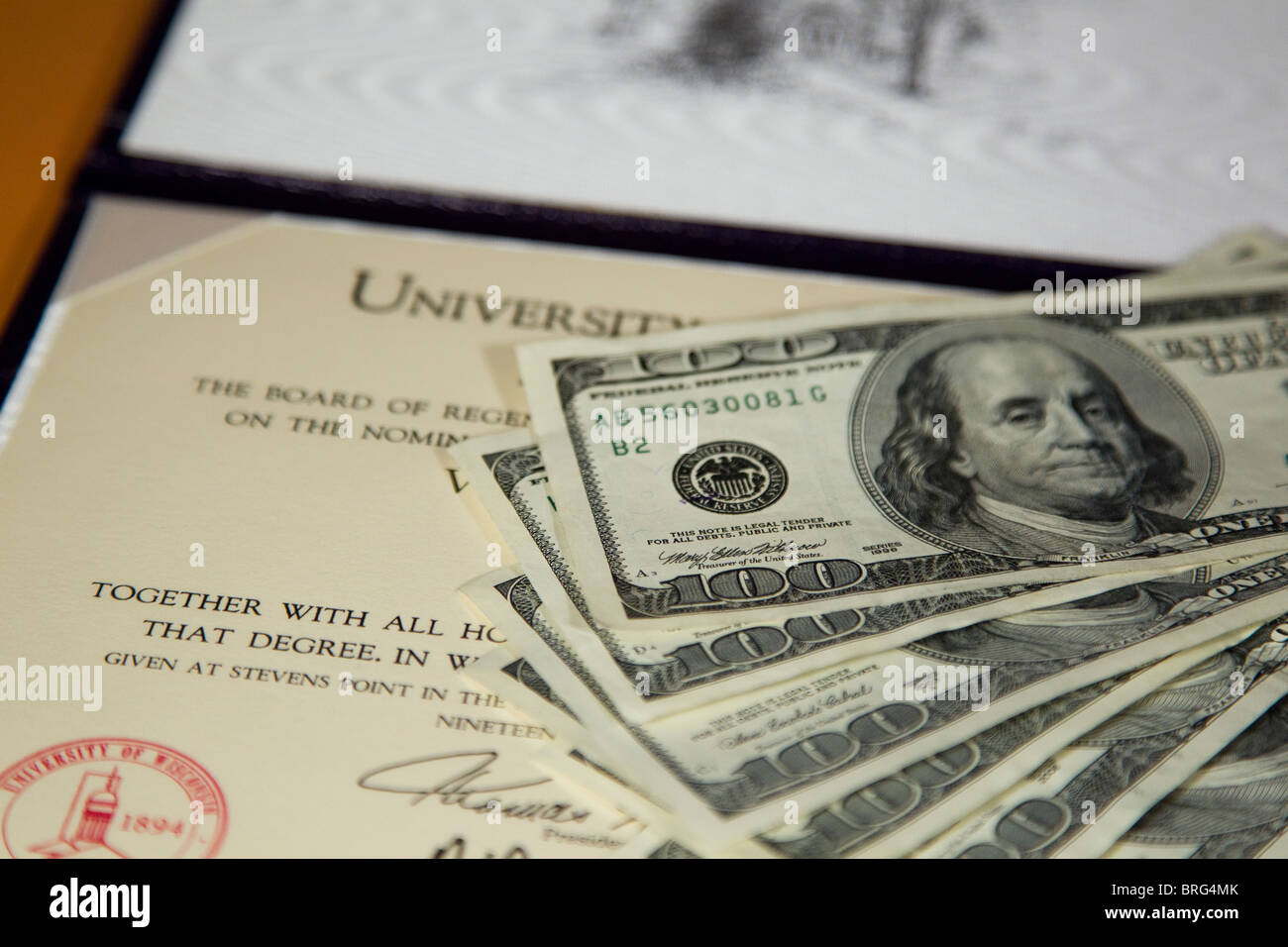 Money and diploma, tuition and fees for college degree - Stock Image