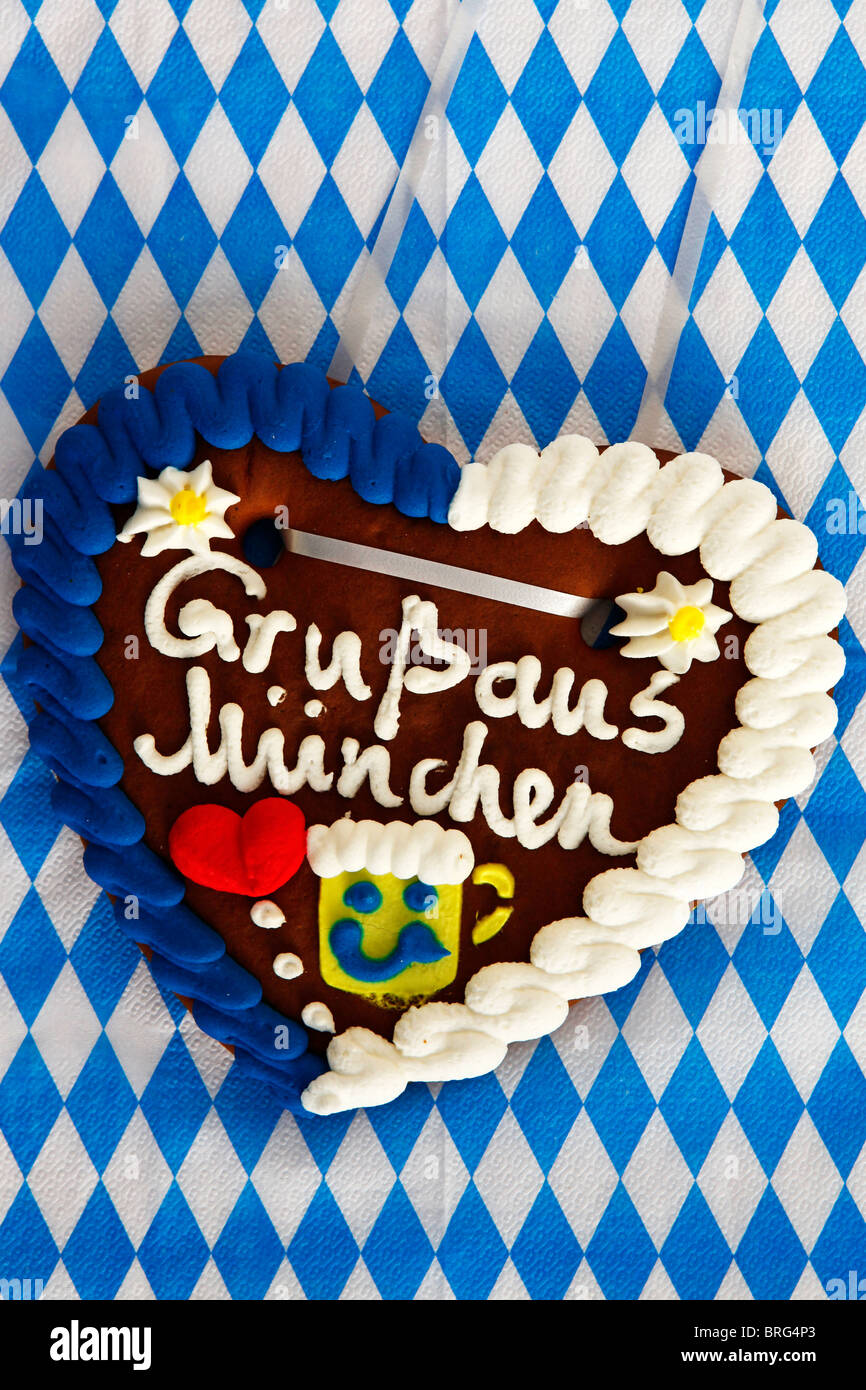 A traditional Bavarian gingerbread heart says 'Gruss aus Muenchen' meaning 'Greetings from Munich'. - Stock Image