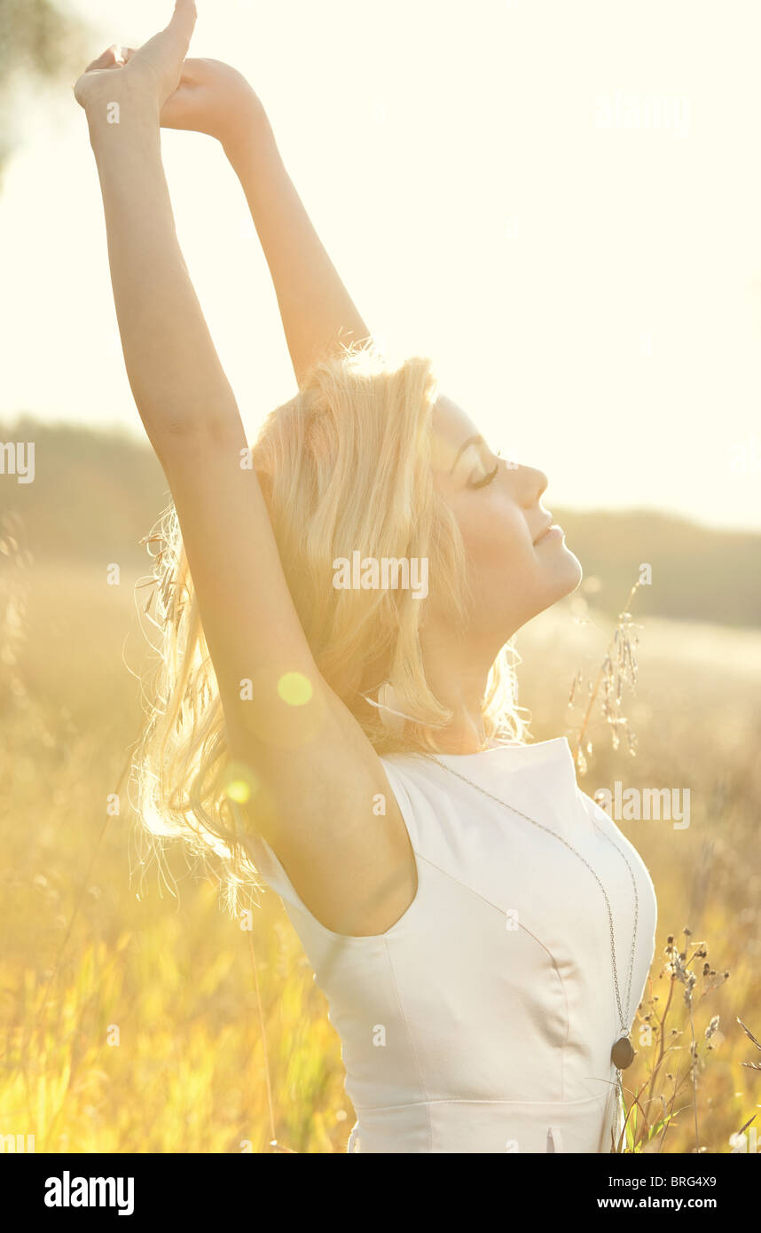 Young woman on summer field portrait. Bright sunlight effect. - Stock Image