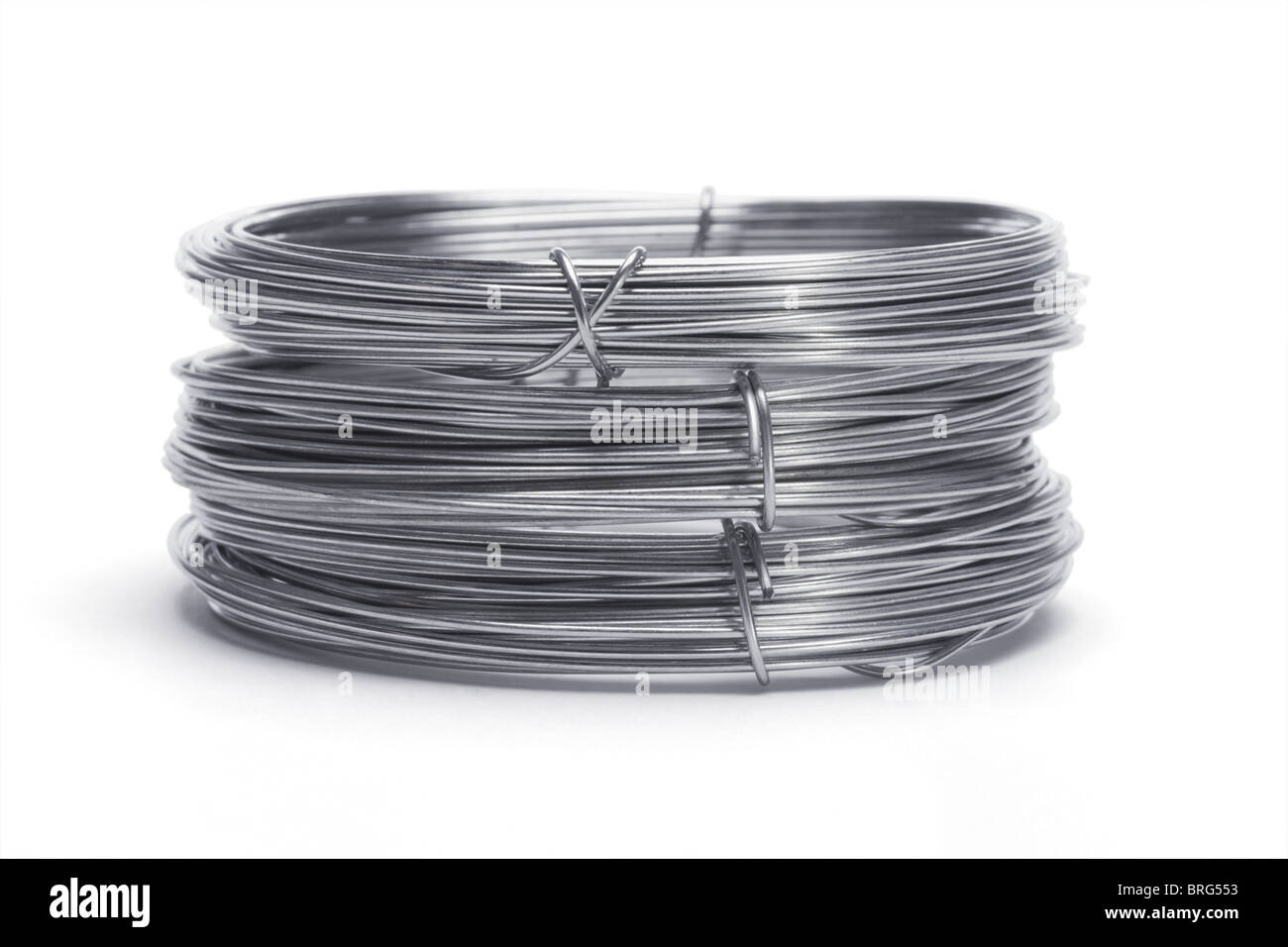 Stack of galvanized wires on white background - Stock Image