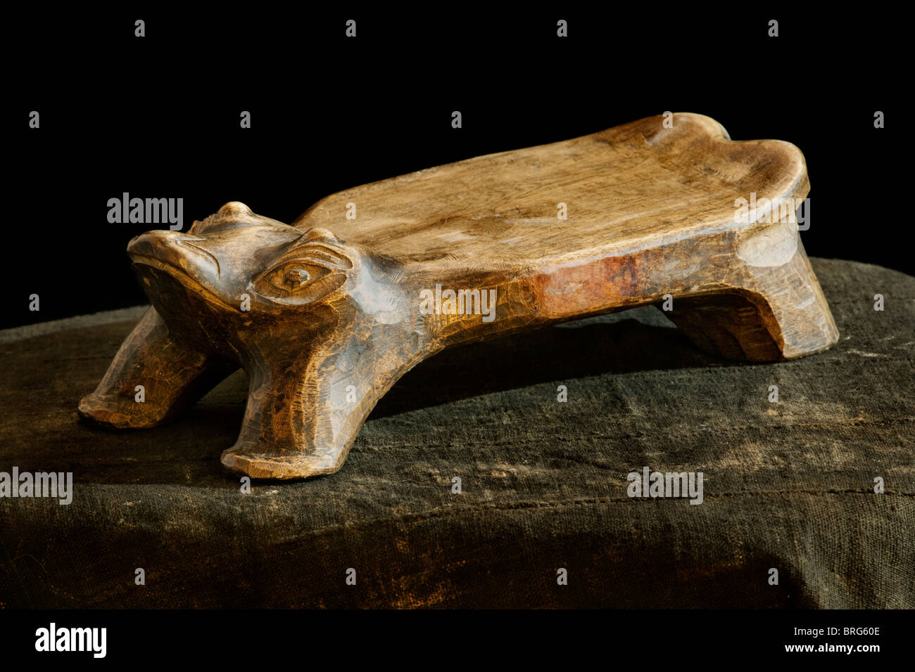Indonesian tribal wooden carved stool in human form idle - Stock Image