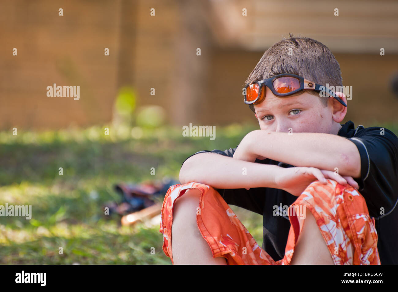 10-yr-old boy wet from swimming watches other swimmers at spring-fed pool. - Stock Image