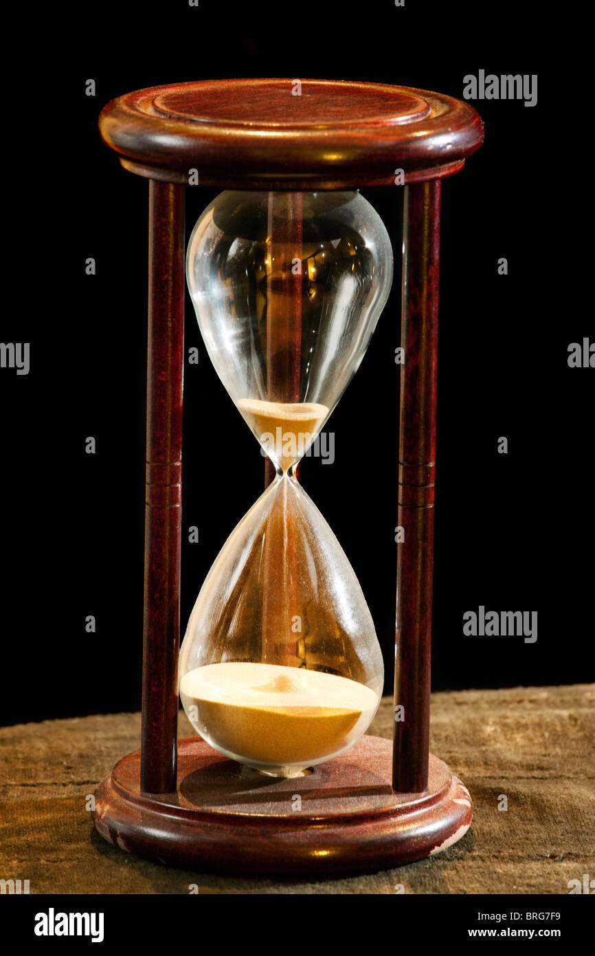 Old Wooden Sand Timer almost out of time on old cloth surface against a black background. Hourglass - Stock Image