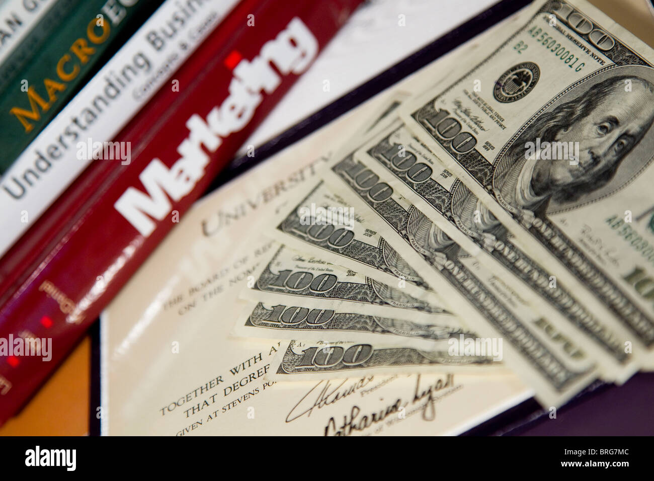 Money, textbooks and diploma, tuition and fees for college degree - Stock Image