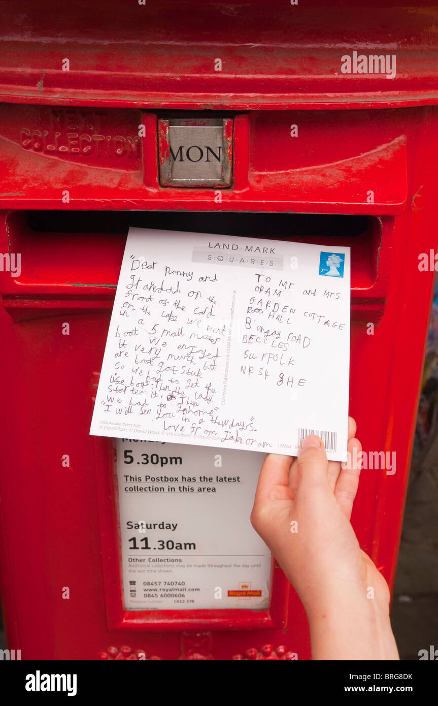 A child posts a postcard into a Royal Mail postbox in the uk - Stock Image