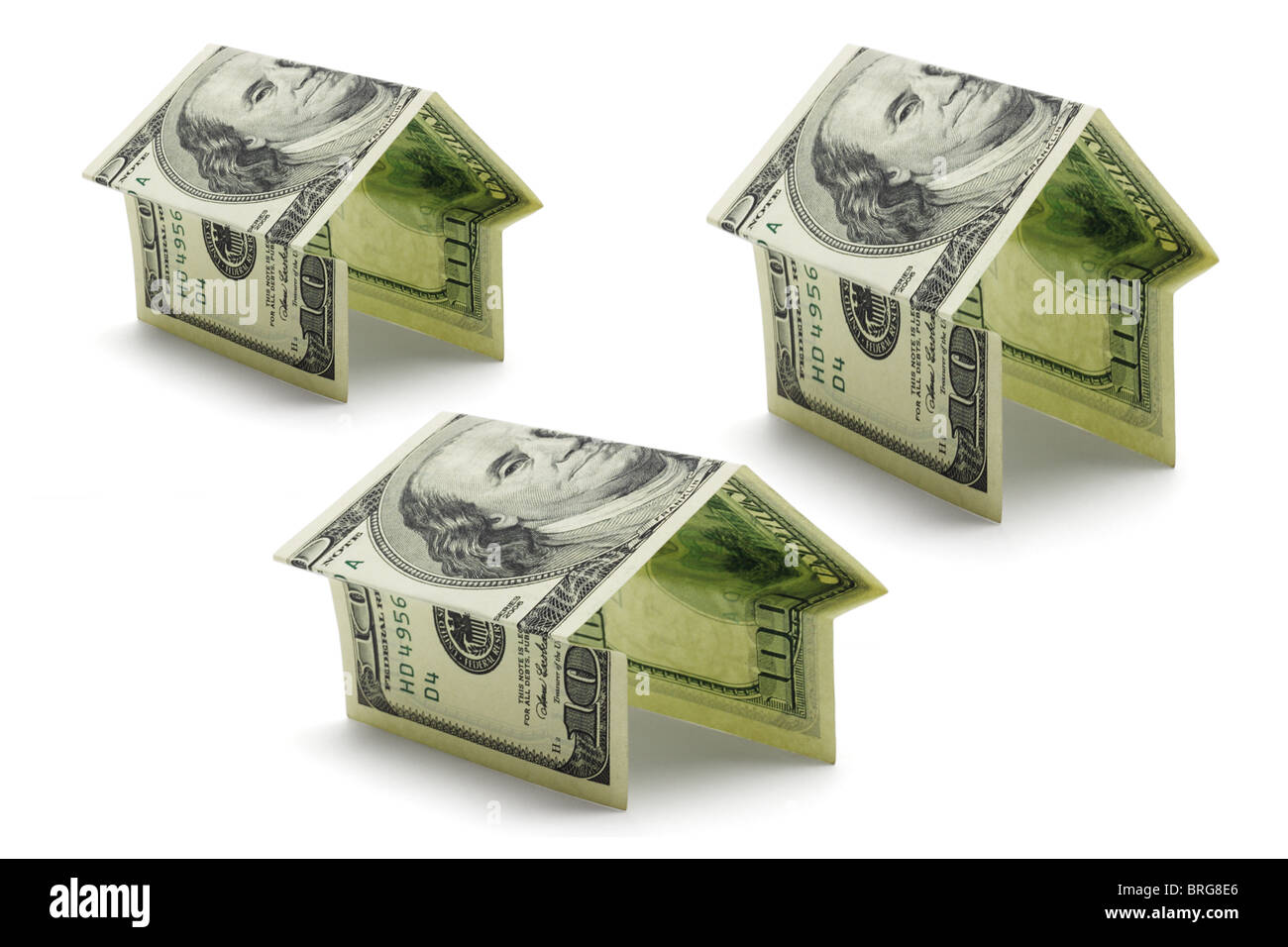 Hundred dollars US notes folded in various shapes and sizes of houses on white background - Stock Image