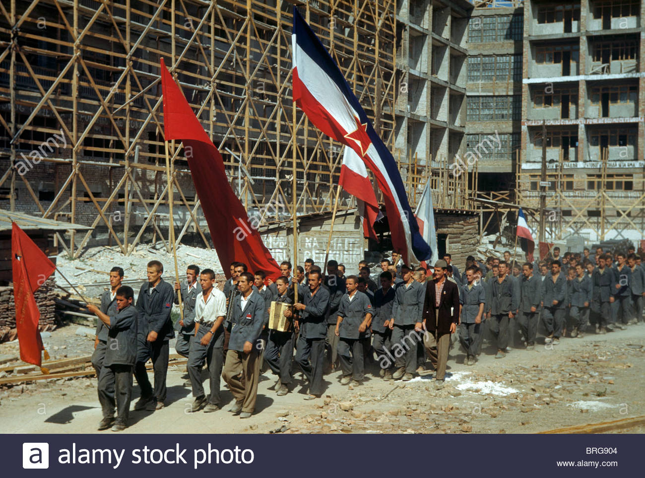 Farmers recruited for construction work march behind flags to lunch. - Stock Image