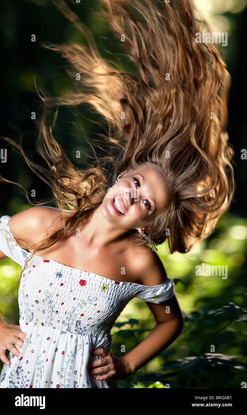 Young smiling woman with fluttering hair. - Stock Image