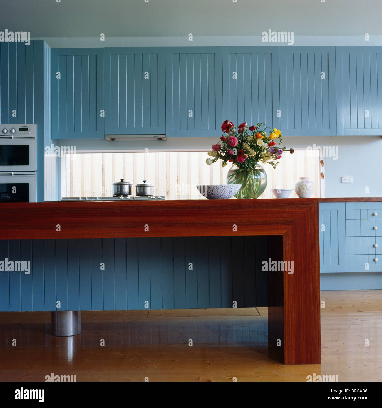 Vase of colorful flowers on wood-finished unit in modern kitchen ...