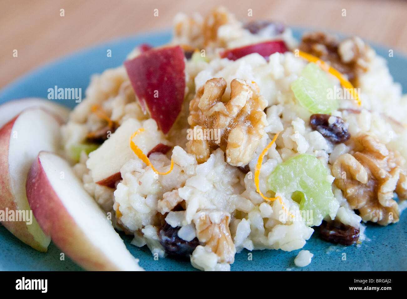 closeup plate of apple walnut brown rice salad on a blue plate with raisins and orange zest topping - Stock Image