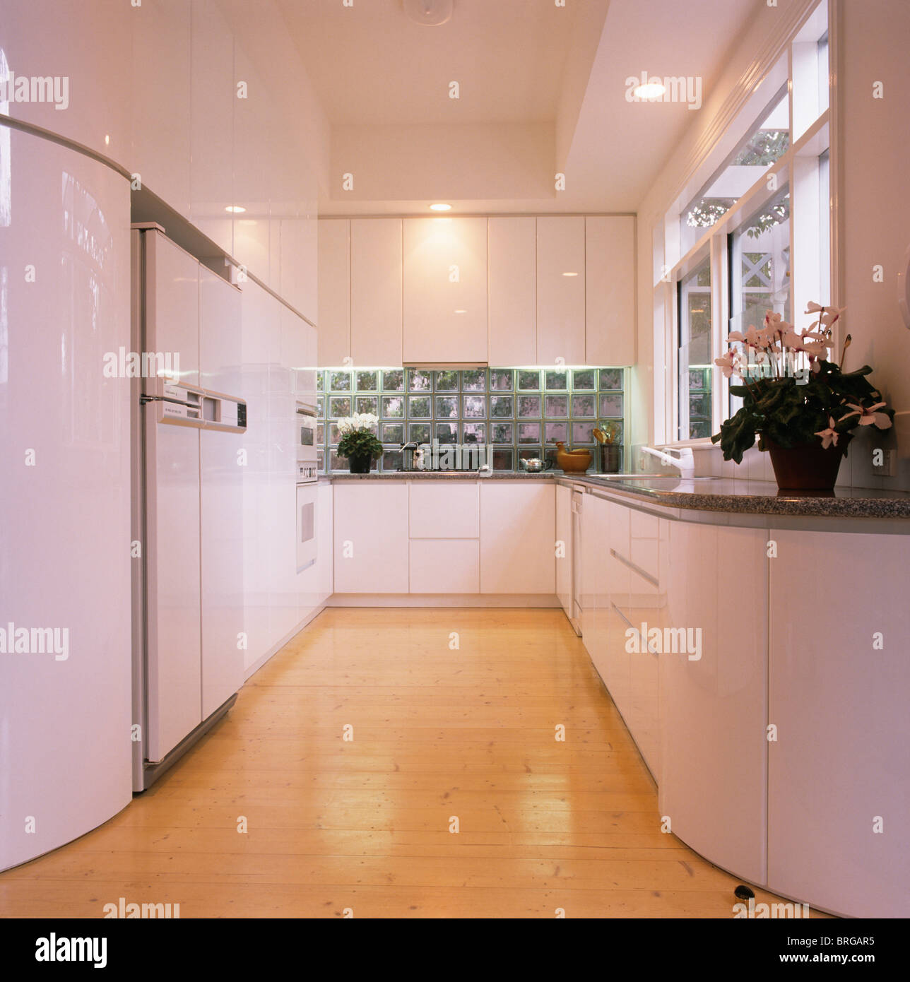 Pale wood flooring in large modern white kitchen with recessed lighting - Stock Image
