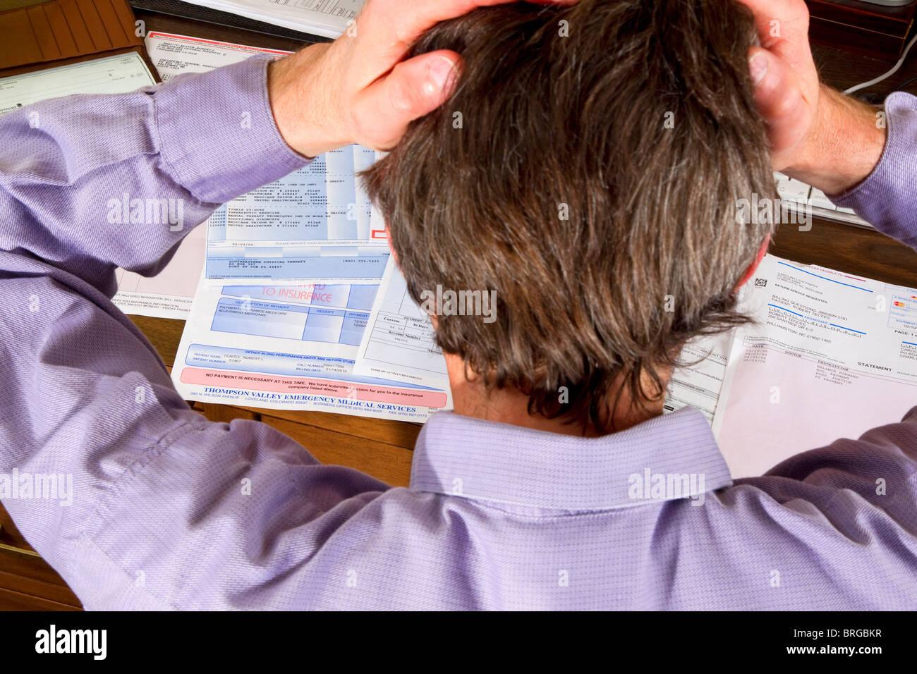 Frustrated man paying bills doing paperwork finances - Stock Image