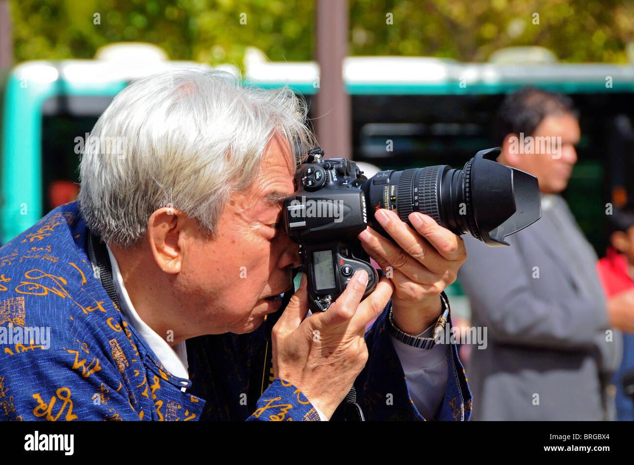 A Japanese tourist with Nikon camera. - Stock Image