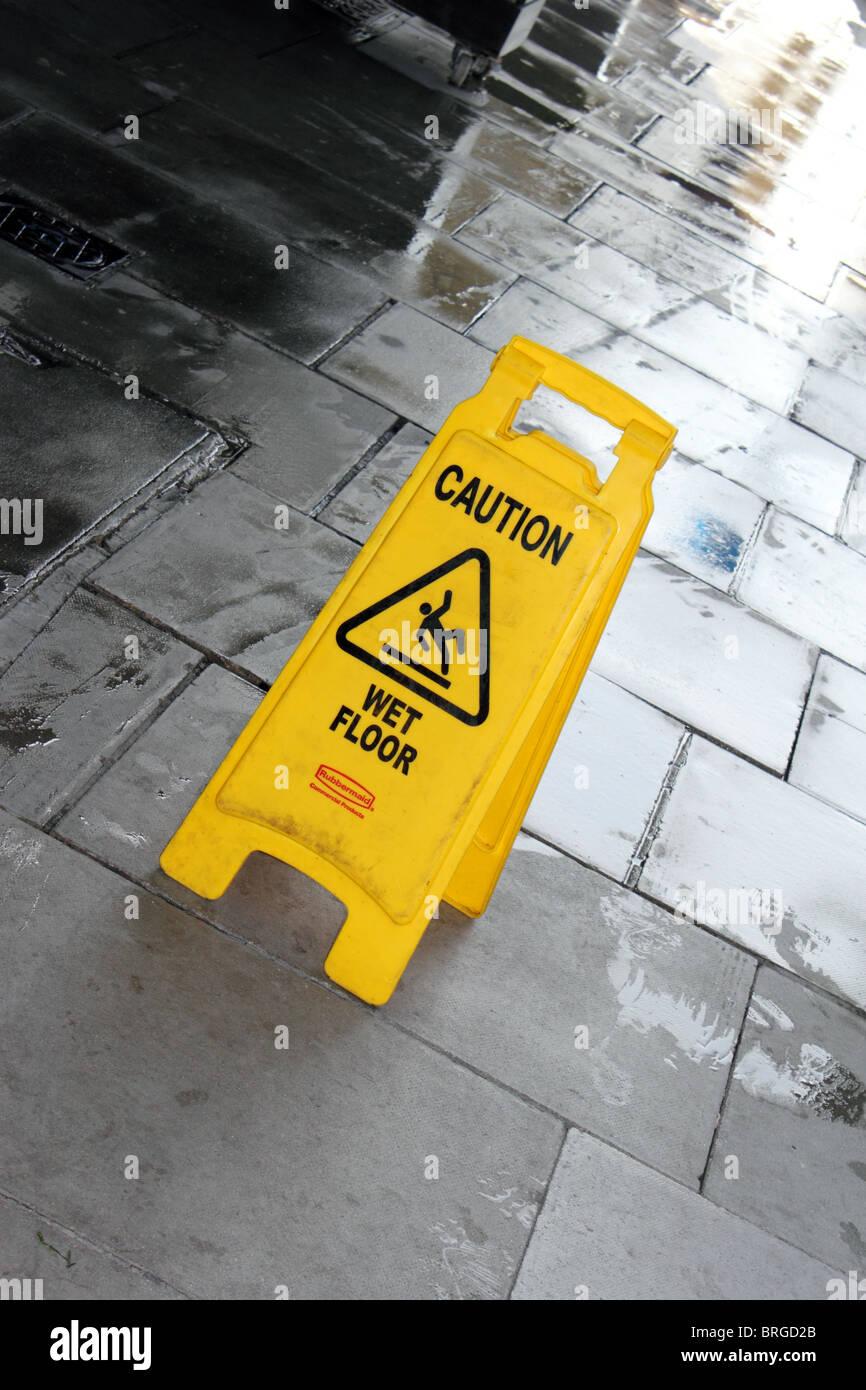 Sign warning pedestrians of wet floor, England, UK - Stock Image