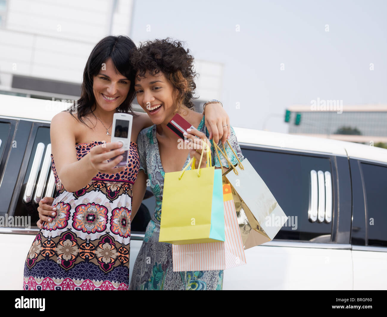 two women standing by limousine and taking picture on mobile phone. Horizontal shape, waist up, copy space - Stock Image