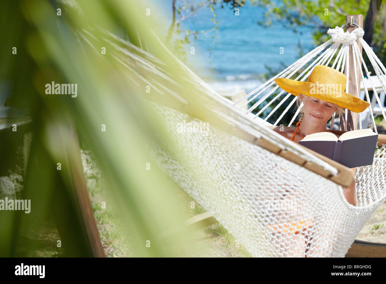 mid adult woman with orange hat reading book on hammock. Front view, Horizontal shape, copy space - Stock Image