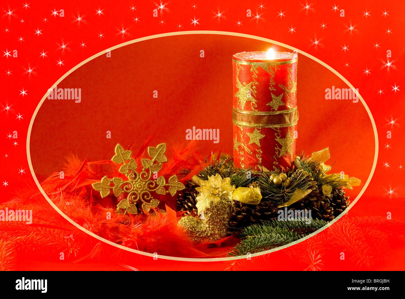 Christmas decorations - red candle, cones, golden snow star, spruce twig and red feathers - Stock Image