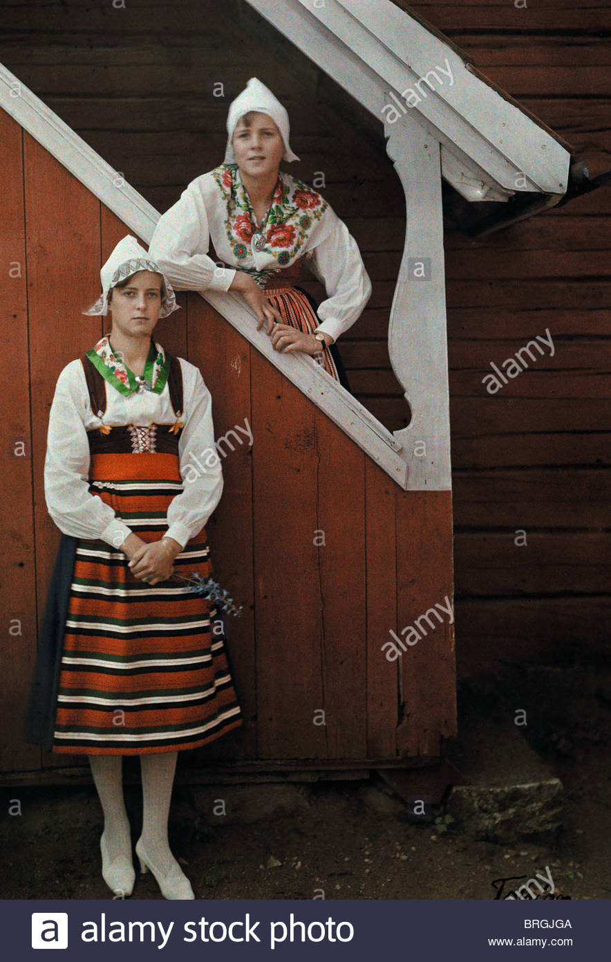 Two nicely dressed Dal girls pose in the doorway of an old farmhouse. - Stock Image