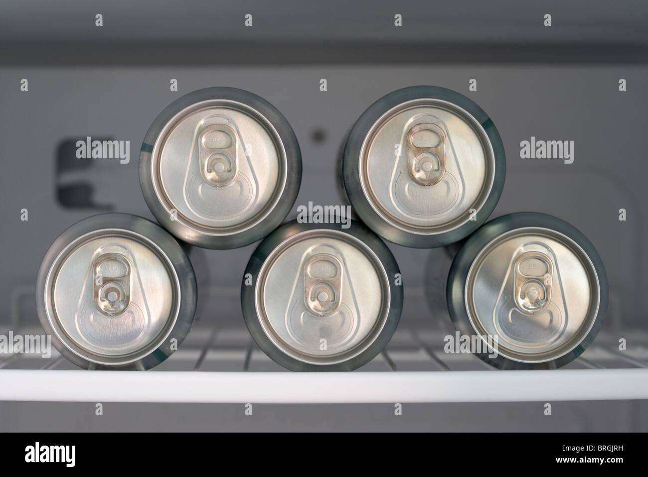 five cans of beer chilling in a fridge - Stock Image