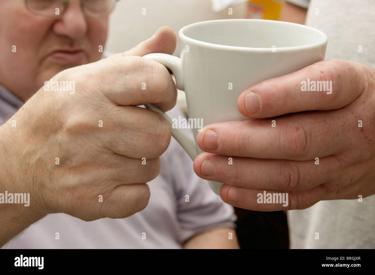 male carer (son) giving a drink to a disabled elderly man - Stock Image