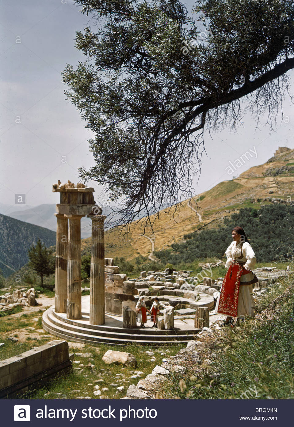 Three restored doric columns stand at the ancient Greek Tholos. - Stock Image