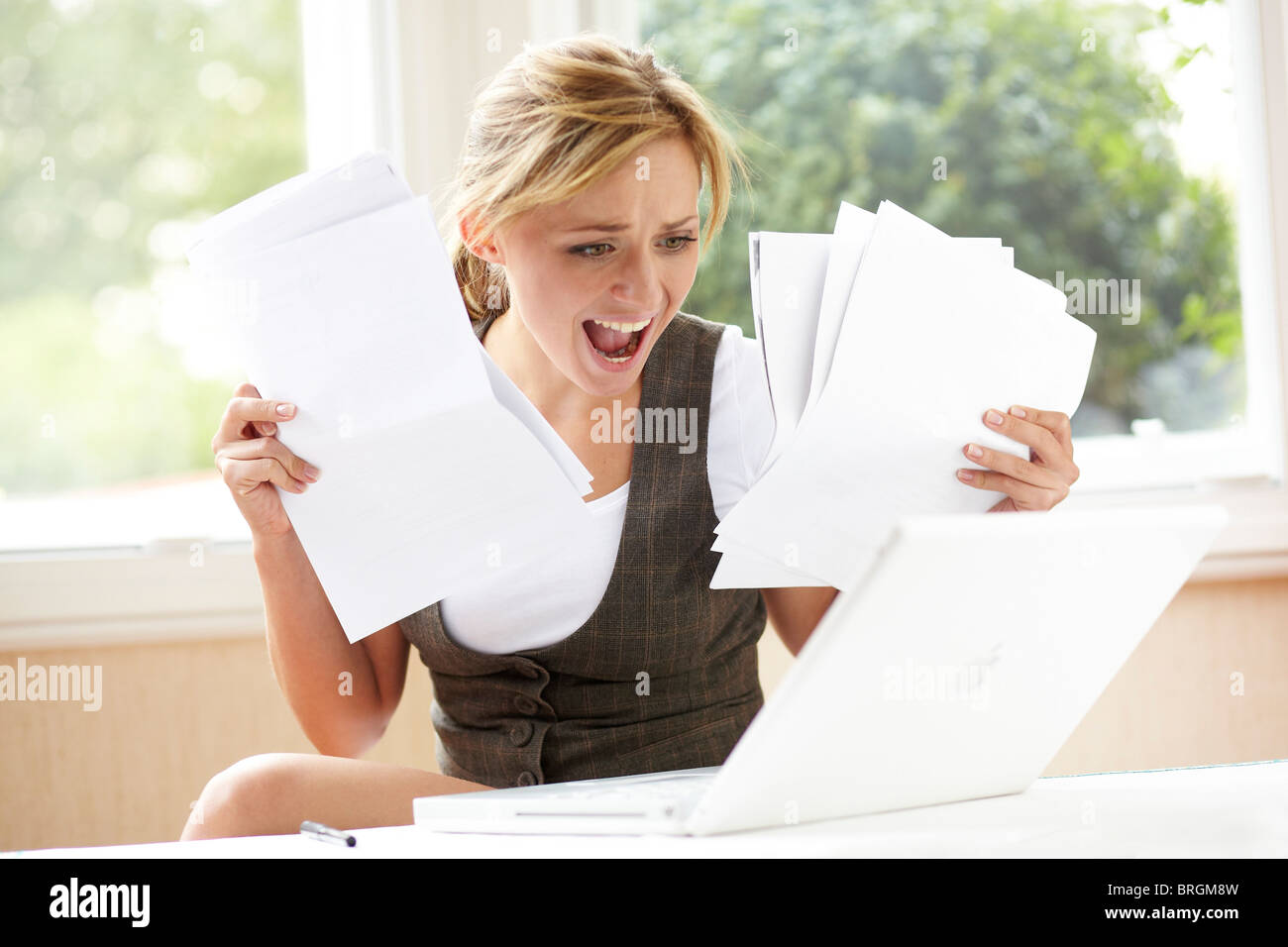 Stressed girl looking at bills - Stock Image