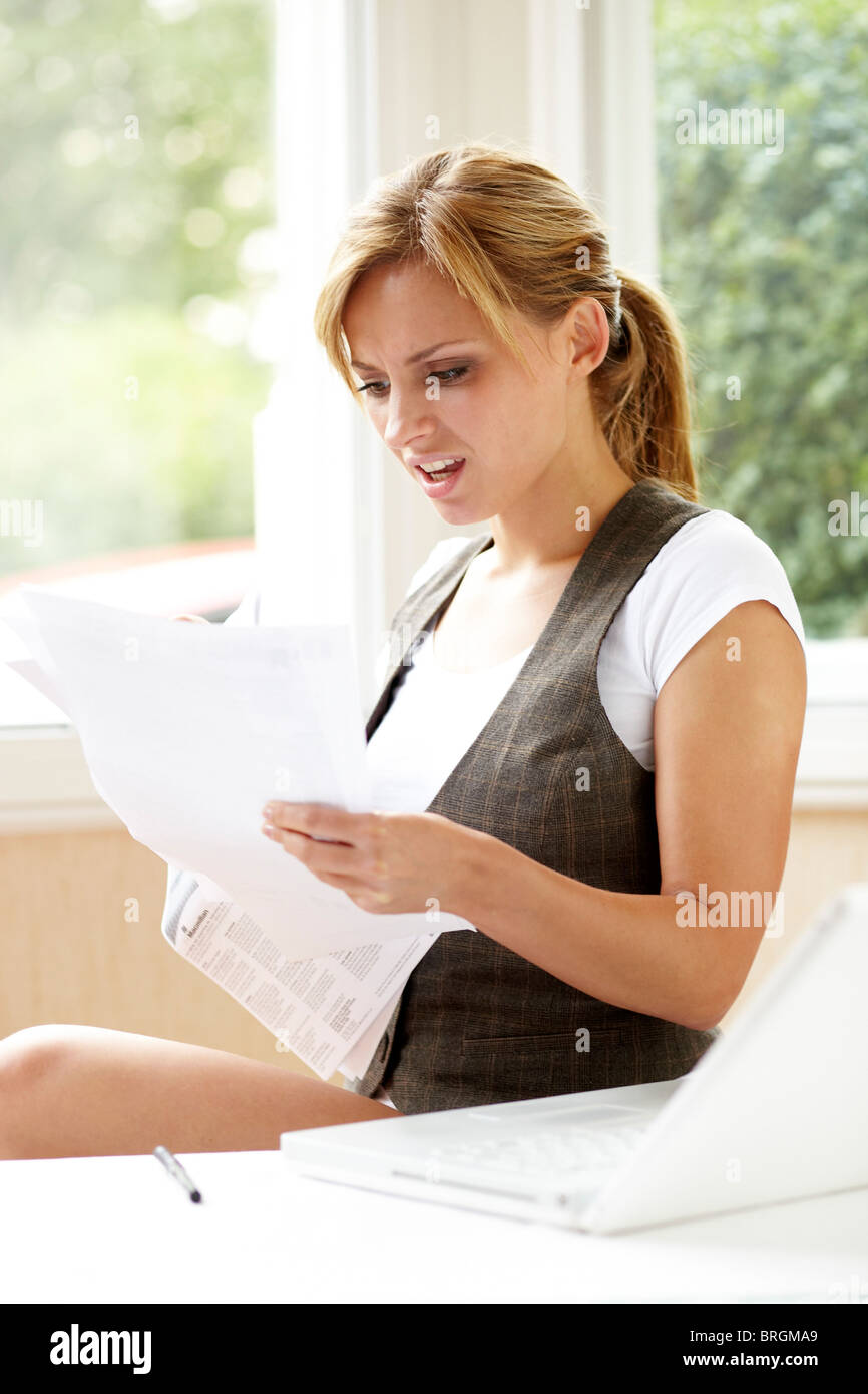 Stressed girl looking at bills Stock Photo