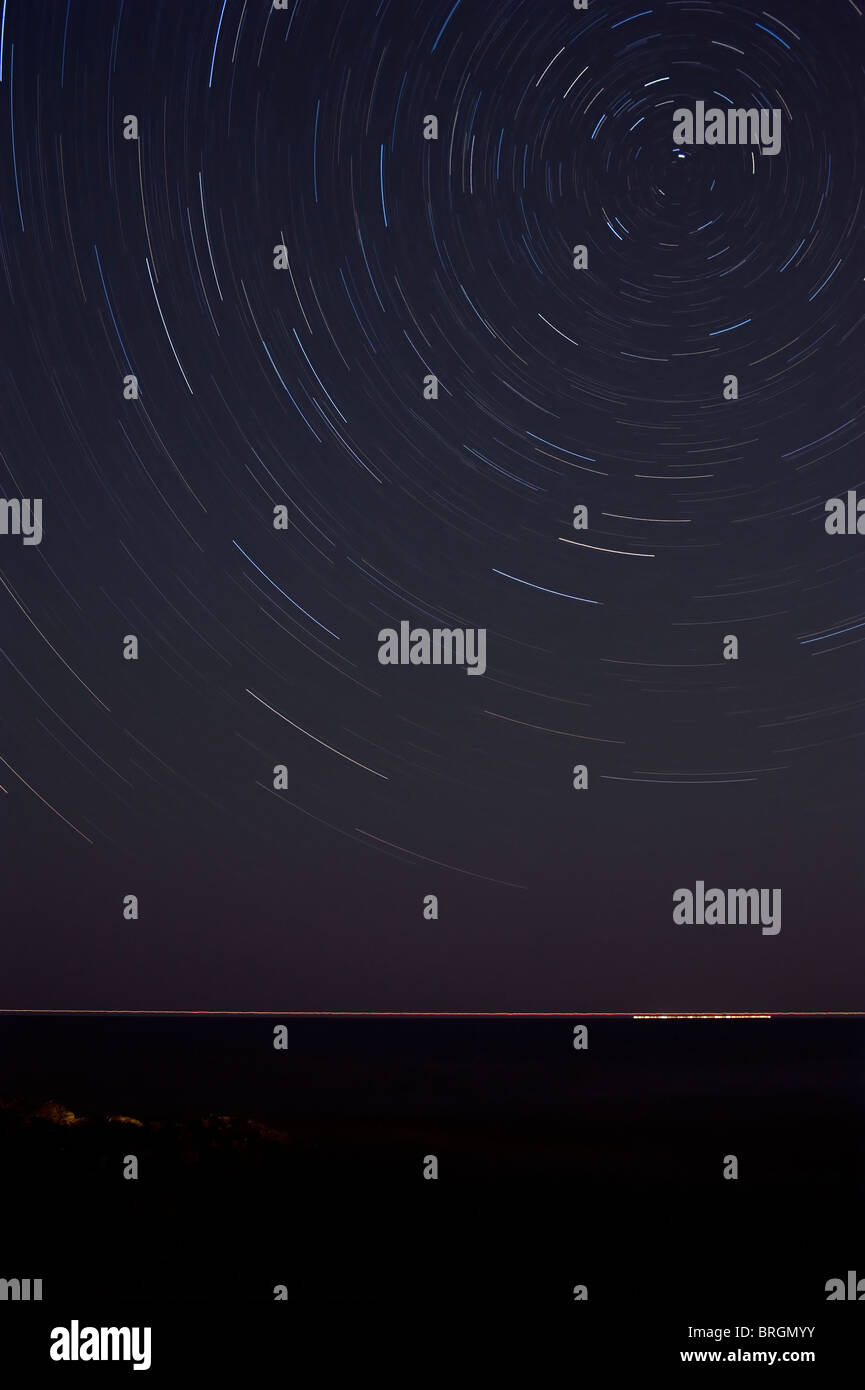 1 hour exposure of passing ship and star trails, Polaris the center of rotation at top right - Stock Image