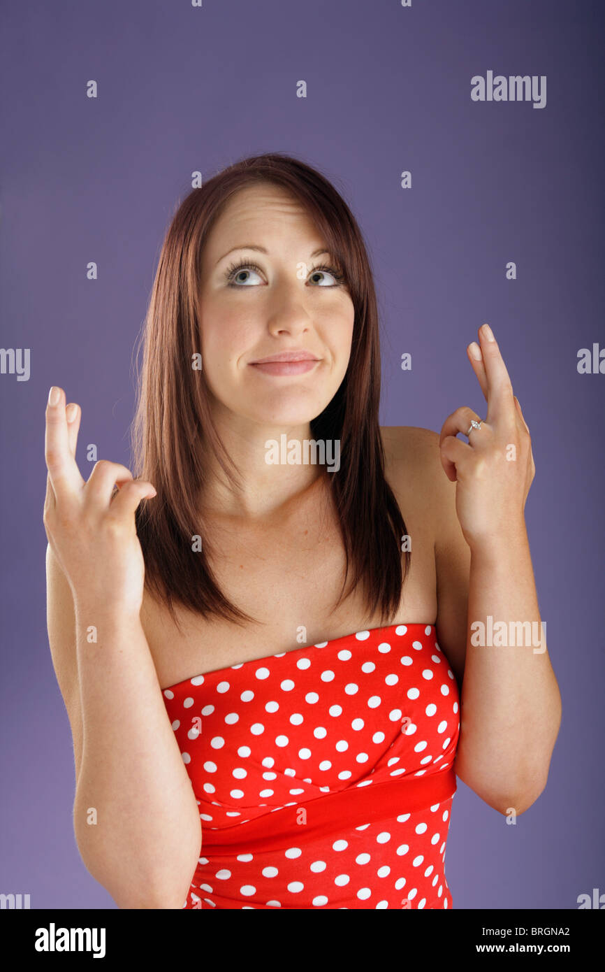 Woman with fingers crossed on both hands - Stock Image