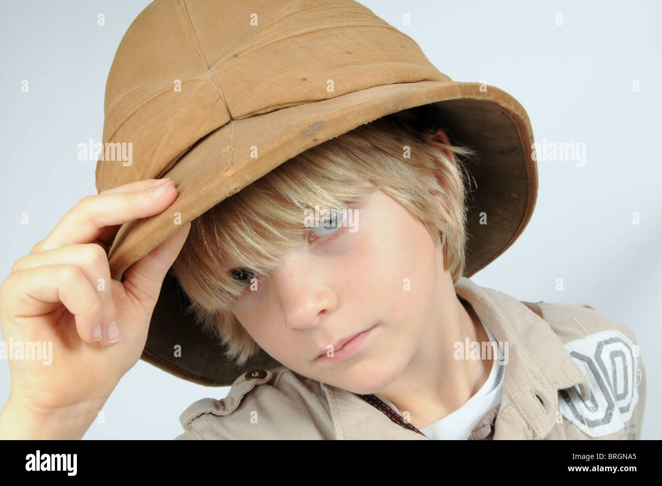 Young boy dressed up as a Victorian explorer wearing a pith helmet looking  serious - Stock 36b8bb2a77a
